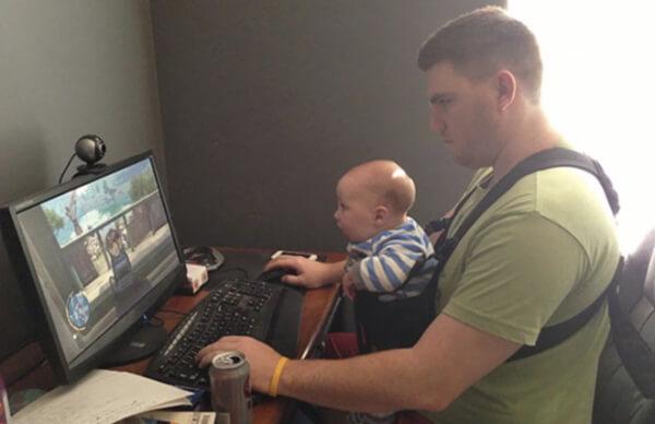 子どもをだっこしながらゲームをしている父親の画像